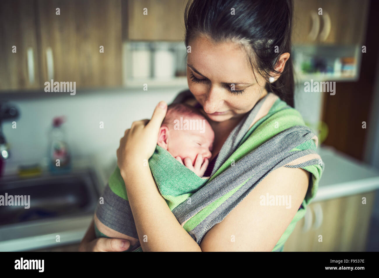 Newborn Baby Hold By Mother In The Baby Wrap Carrier Stock Photo