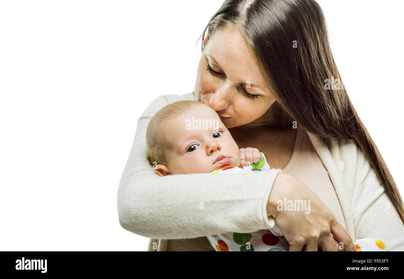 Mother holding a baby in her arms and kissing it tenderly isolated on white background - Stock Image