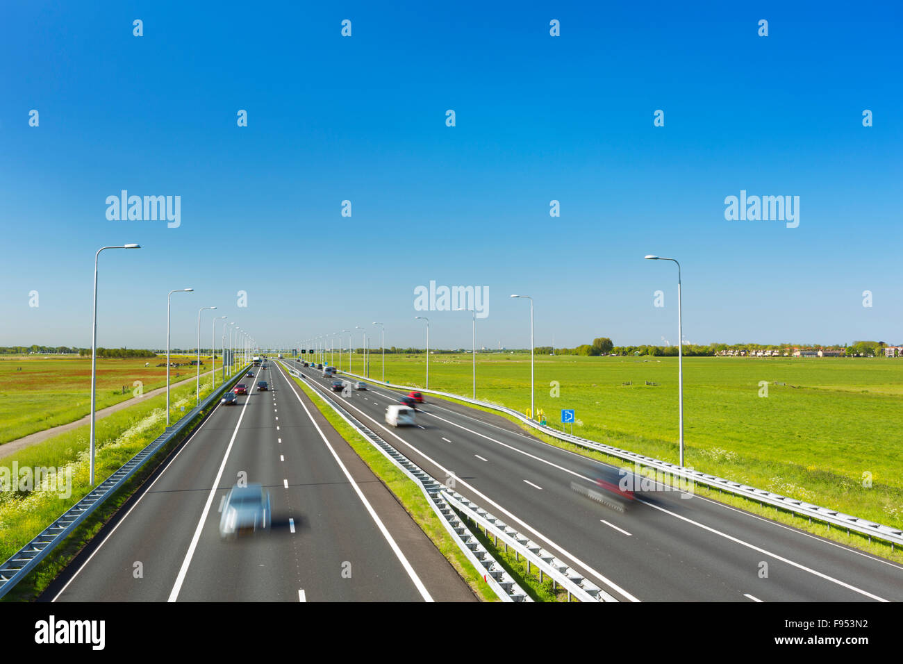 A highway with traffic through grassy fields on a bright and sunny day in The Netherlands. - Stock Image