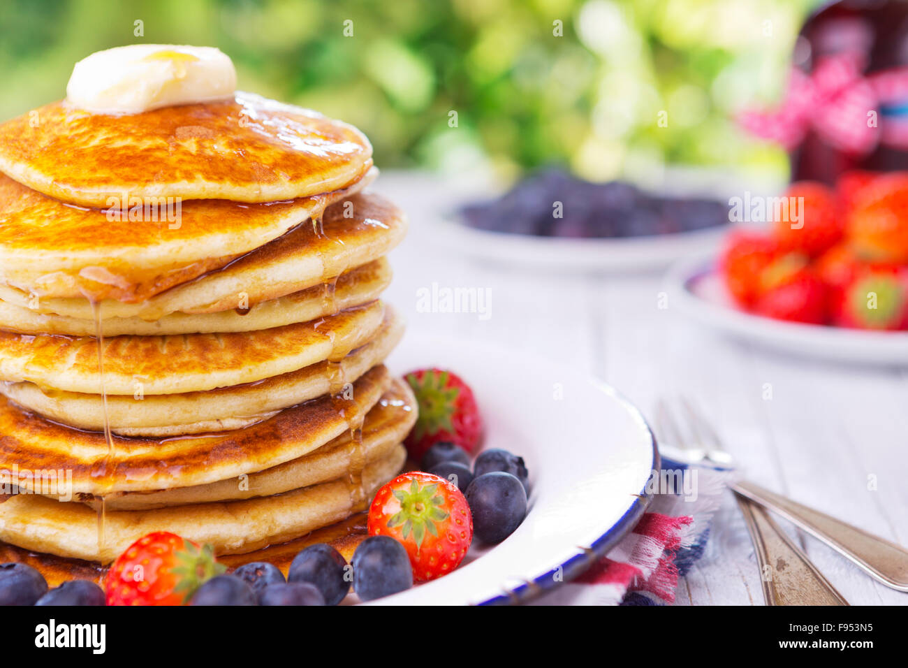 A stack of homemade pancakes with fresh fruit, butter and syrup. - Stock Image