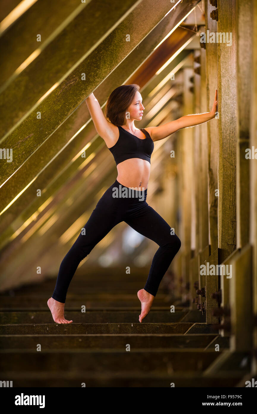 1b4e4600dc Healthy lifestyle and well-being  A young woman wearing a black sports bra  and leggings exercising keeping fit balancing on her feet