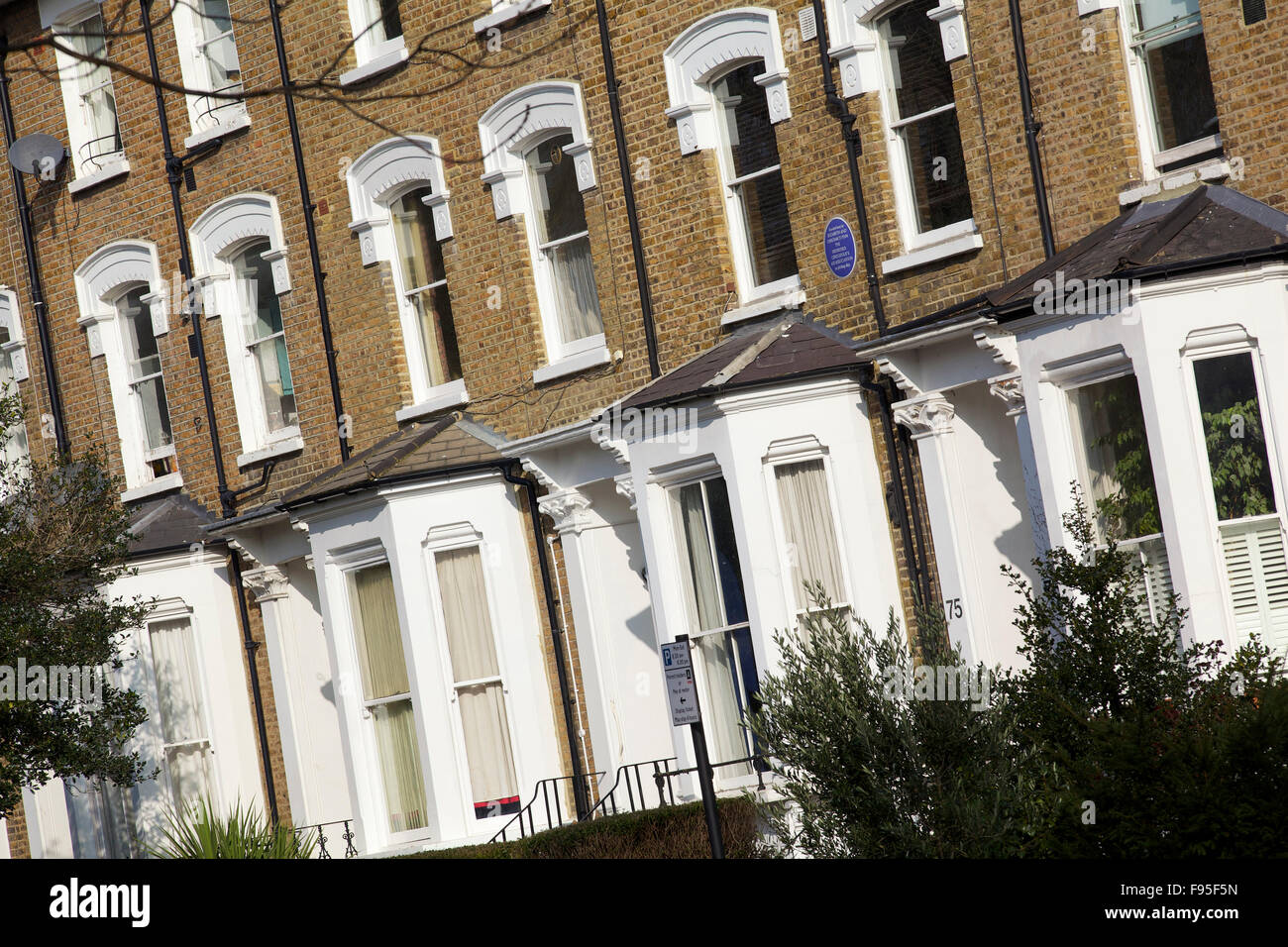 Hammersmith, London. Angled view of row houses in a residential street in Hammersmith. Bay windows. Brick used on - Stock Image