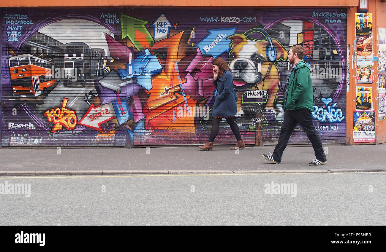 Young man and woman walking past some street art on shutters in Stevenson Square, Lever Street, Manchester city Stock Photo