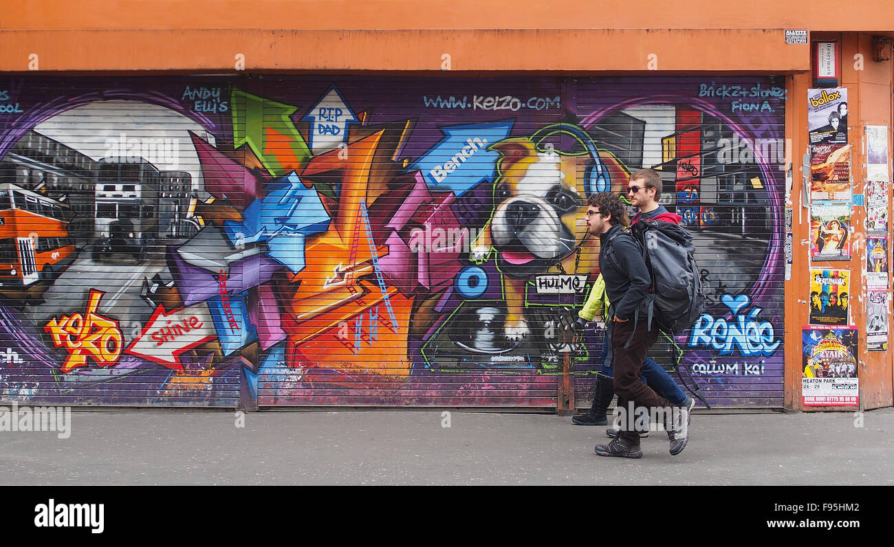 3 young men walking past some street art on shutters in Stevenson Square, Lever Street, Manchester city centre, Stock Photo