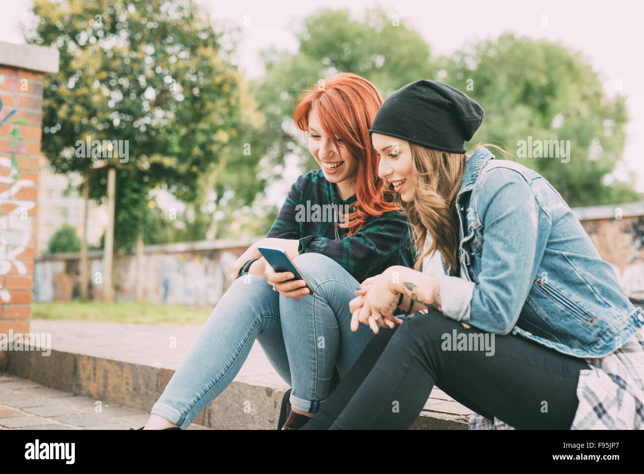 Two young handsome caucasian blonde and redhead straight hair women sitting on a staircase using smartphone, looking - Stock Image