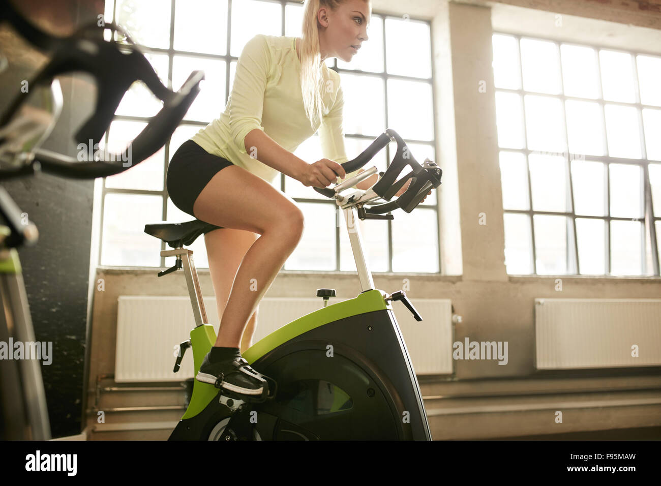 Fitness woman on bicycle doing spinning at gym. Fit young female working out on gym bike. - Stock Image
