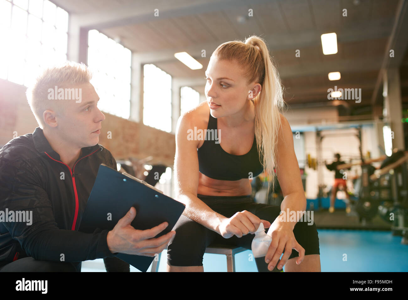 Shot of a personal trainer and young woman discussing fitness plan. Personal trainer showing something on clipboard - Stock Image