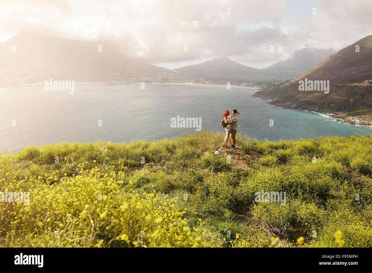 Outdoor shot of romantic young couple standing at the top of a peak. Couple standing close to each other looking - Stock Image
