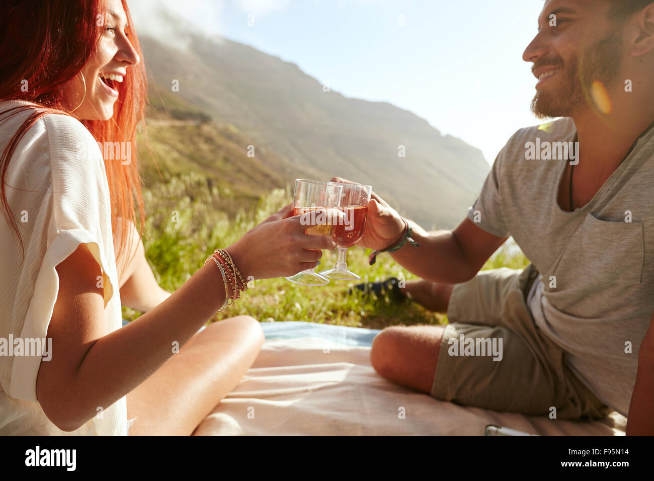 Shot of a cheerful young couple drinking wine and enjoying a picnic.  Young man with her girlfriend on vacation sitting on grass Stock Photo