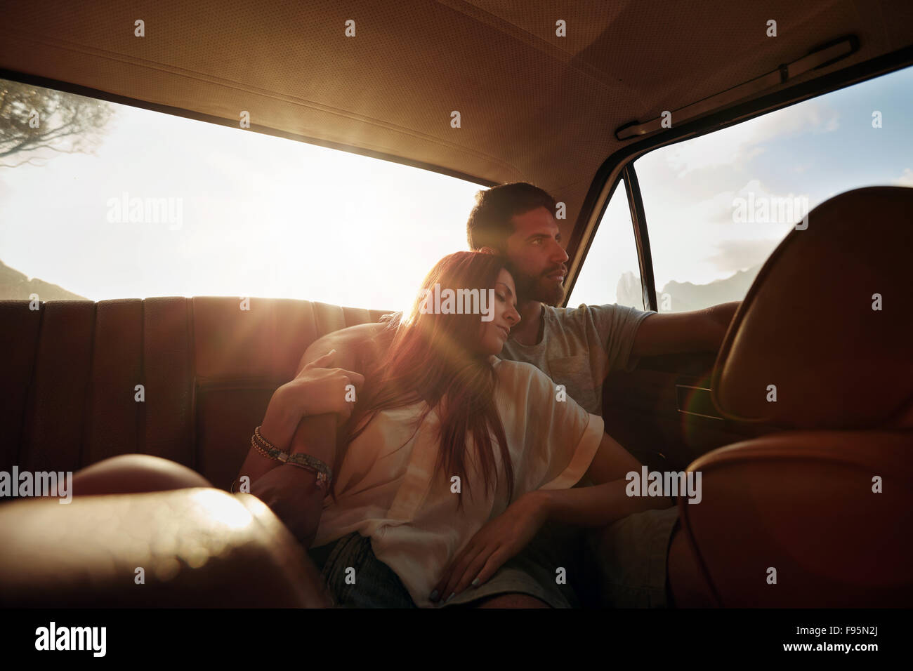 Shot of young couple relaxing in rear seat of car. Man and woman on road trip during summer. - Stock Image