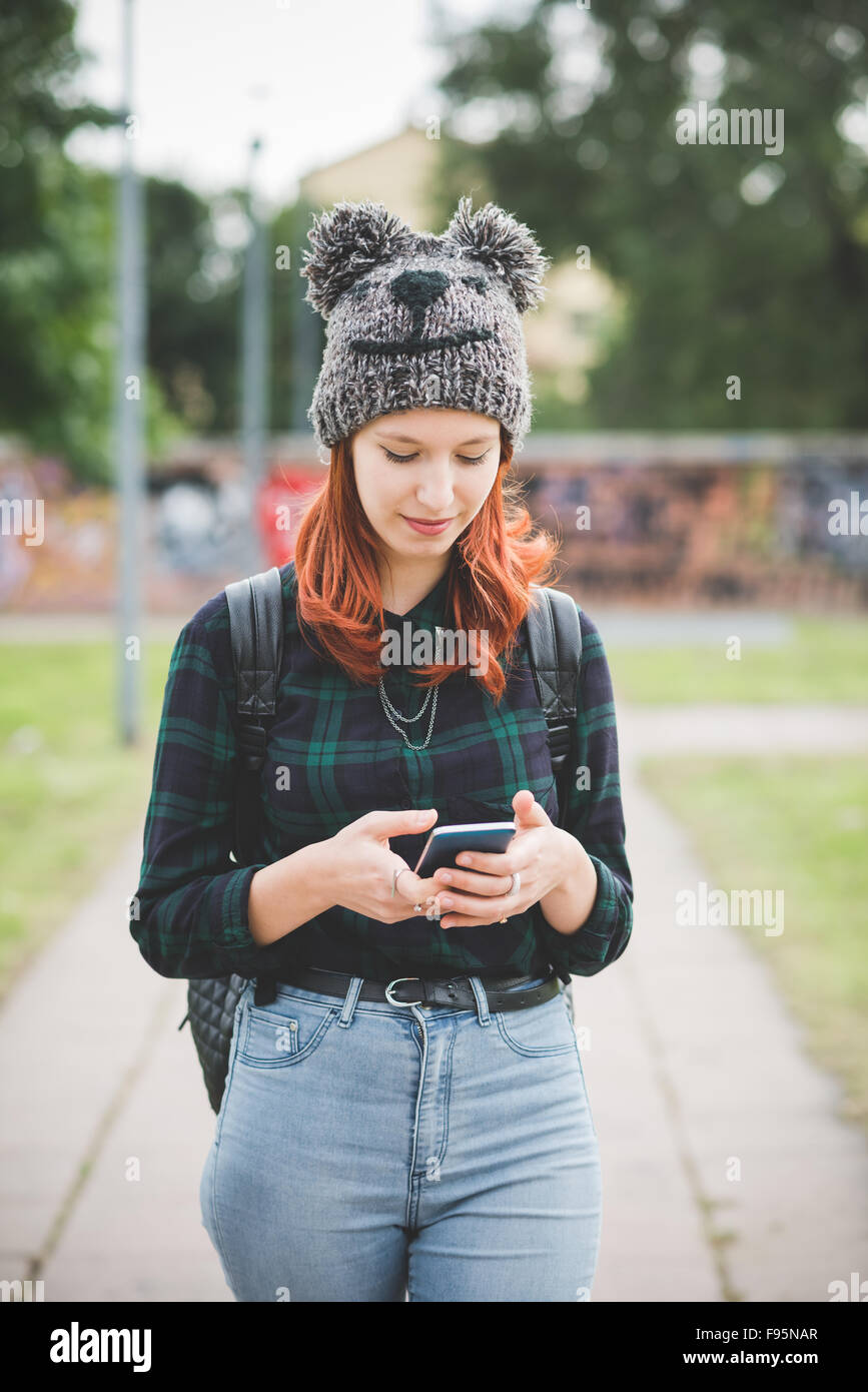 Knee figure of young handsome caucasian redhead straight hair woman walking in the city, holding smartphone, tapping - Stock Image
