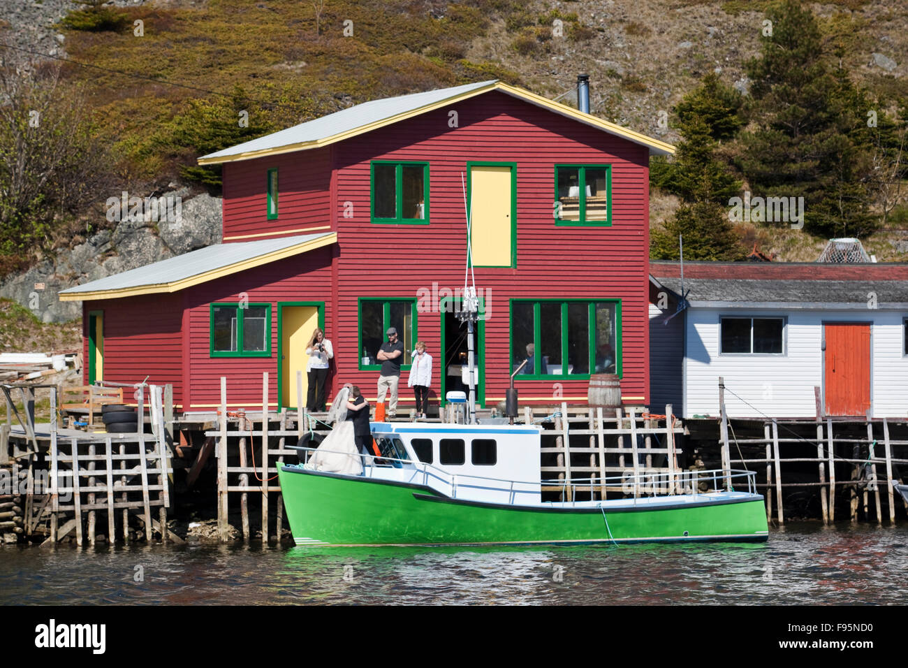 Newlyweds posing for photos on a bightly coloured fishing boat moored next to a fishing shed in Quidi Vidi, Newfoundland, - Stock Image