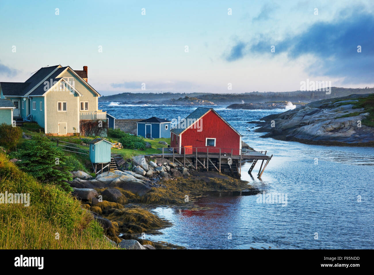 Seaside home across from rocks and crashing waves in Peggy's Cove, Nova Scotia - Stock Image