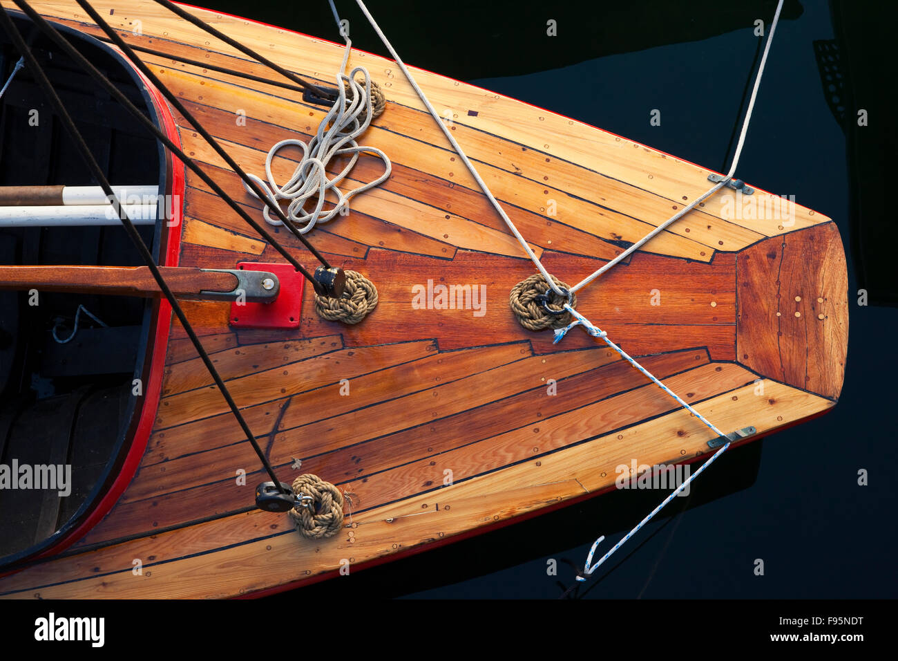 View from above of the bow of a small wooden sail boat. - Stock Image