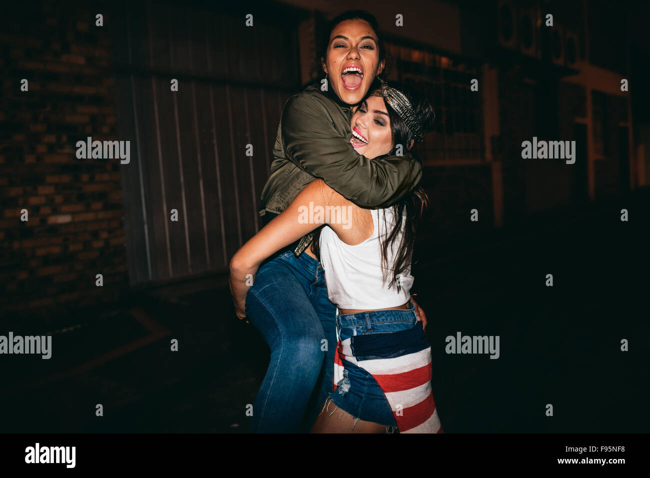 Night shot young woman lifting her best friend laughing. Female friends hanging out and having fun. - Stock Image