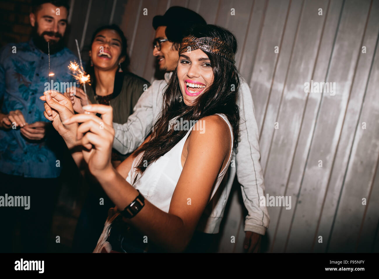 Shot of a young woman playing with sparklers at night. Best friends celebrating 4th of july outdoors. Stock Photo