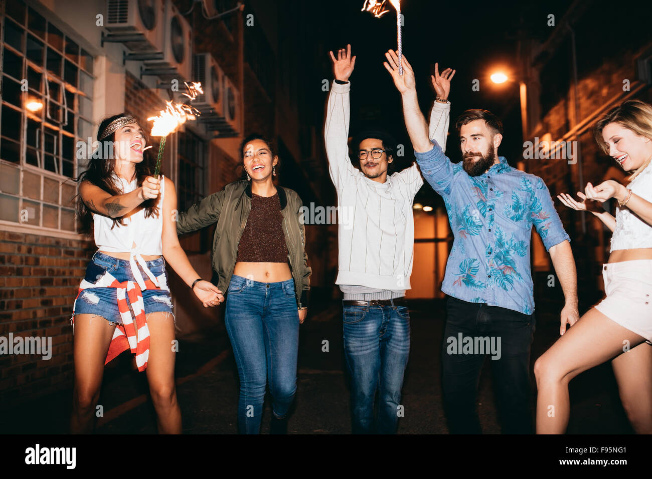 Portrait of happy young friends celebrating new years eve with sparklers at night. Best friends hanging out at night - Stock Image