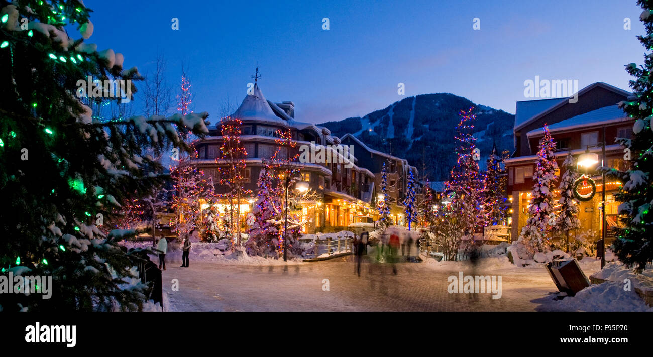 The lights of Christmas sparkle in Whistler Village on a winter evening. - Stock Image