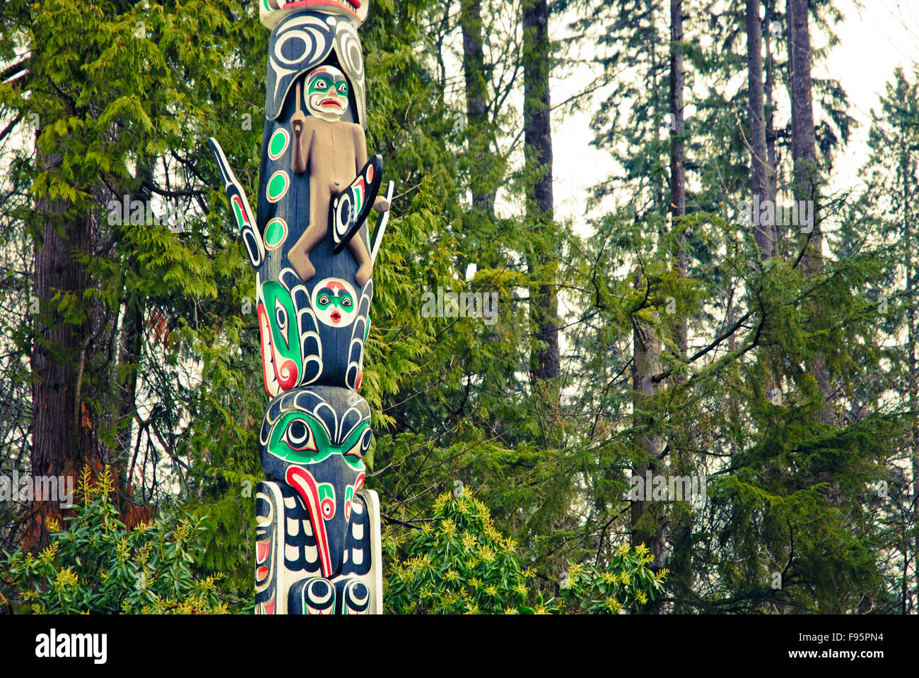 Native peoples totem pole standing in Stanley Park, Vancouver, British Columbia, Canada - Stock Image