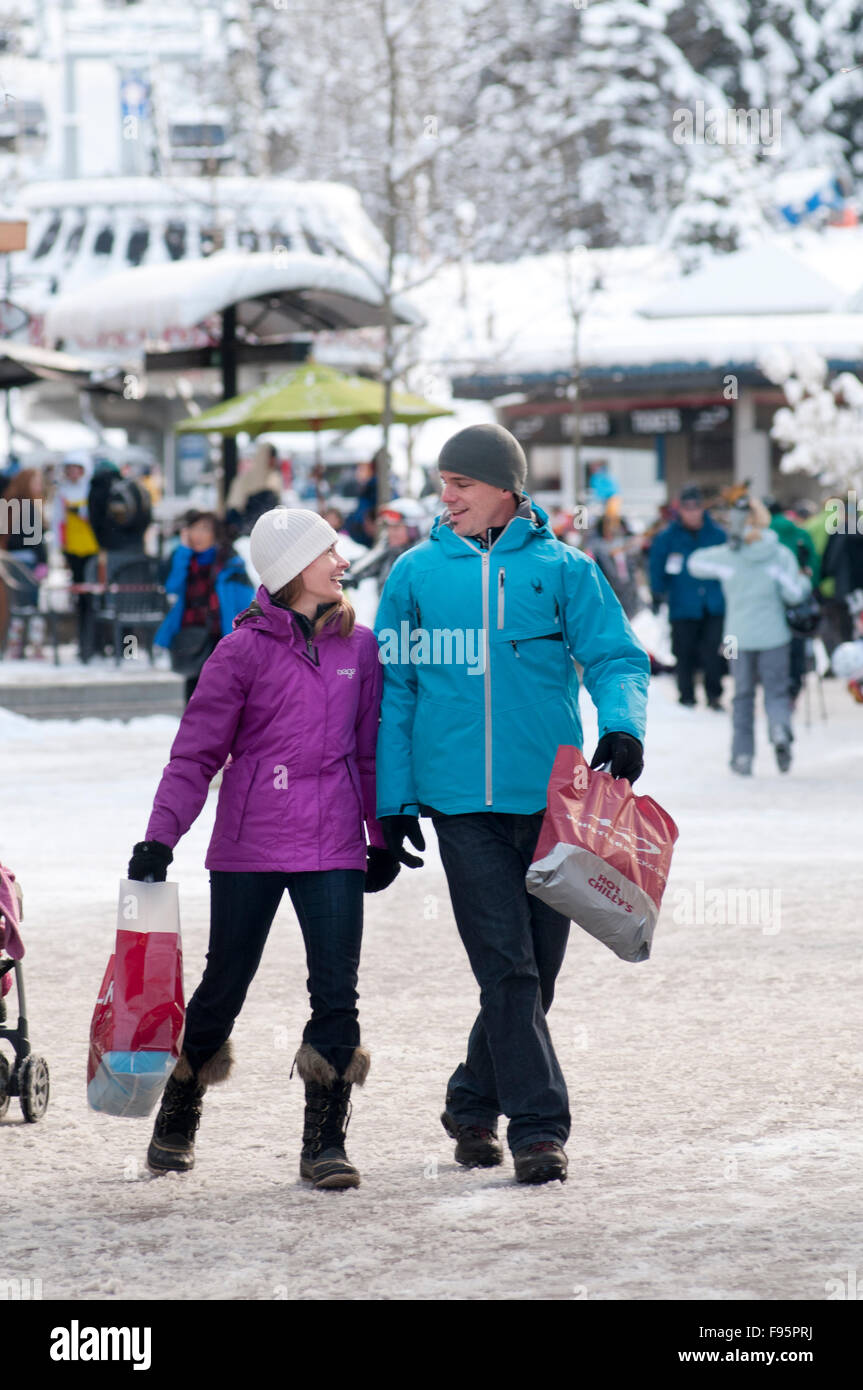 A couple enjoys strolling and shopping Whistler village on a winter day. - Stock Image