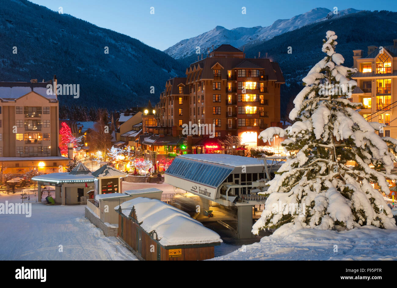 Whistler Village glows with lights at sunset on a winter evening - Stock Image