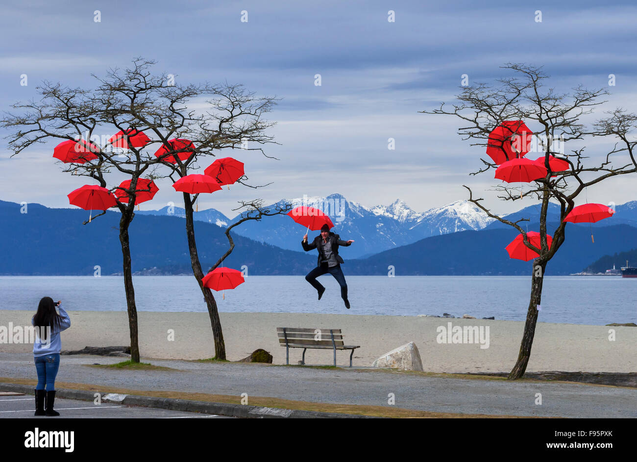 Outdoor umbrella art display with jumping man being photographed Spanish Banks, Vancouver, British Columbia, Canada - Stock Image