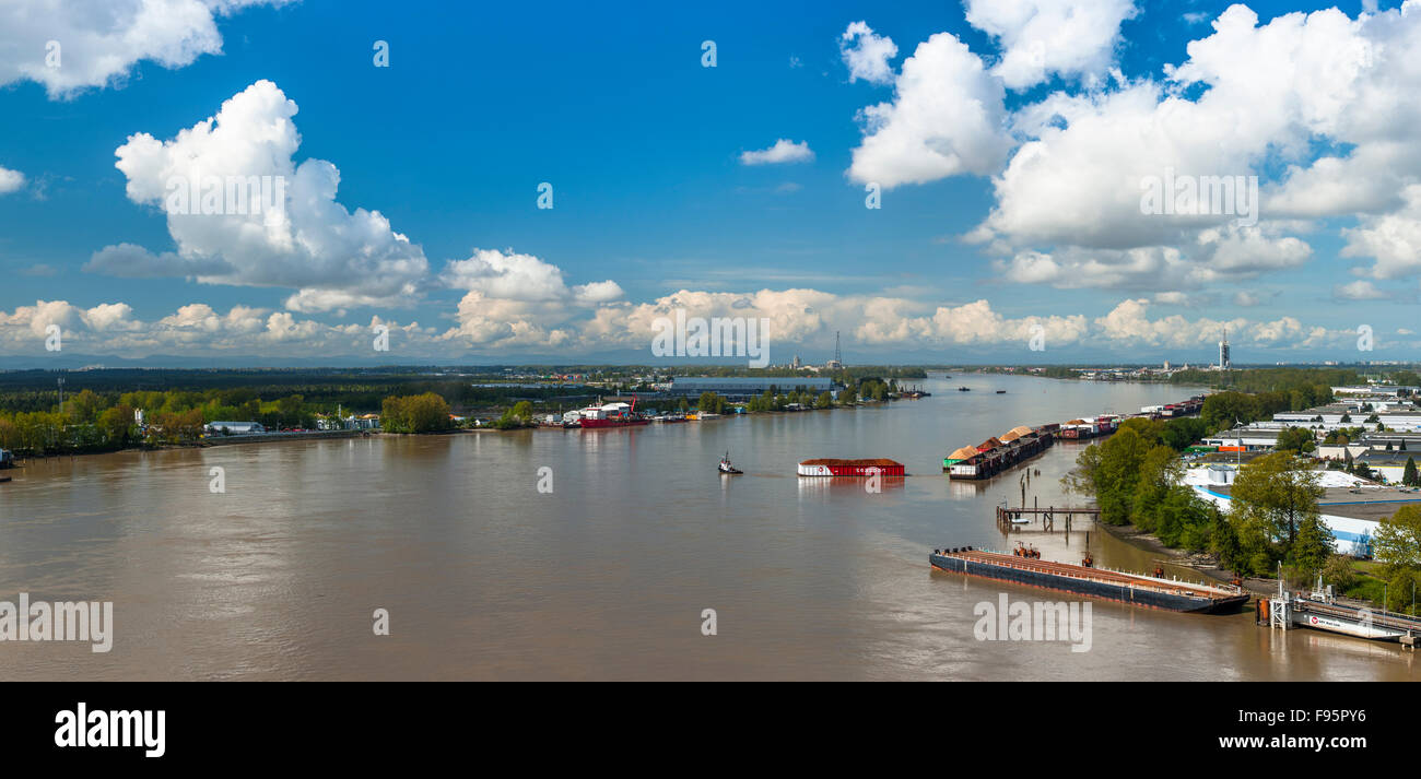 Tugboat pulling barge full of woodchips on the Fraser River. - Stock Image