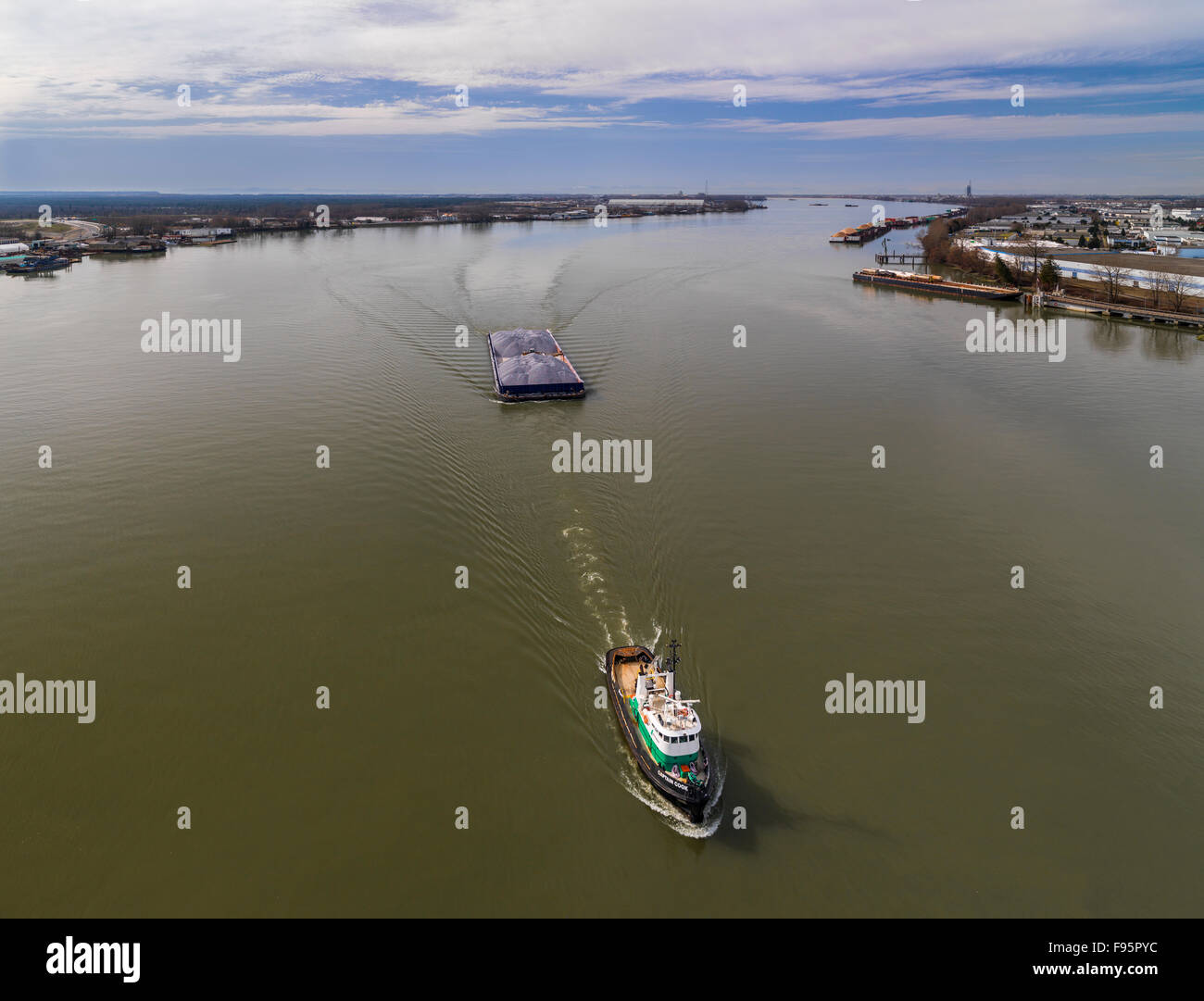 Tugboat pulling barge full of gravel up the Fraser River - Stock Image