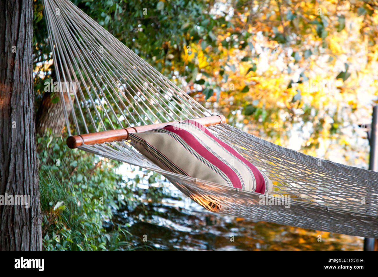A hammock waits for a lazy afternoon by Langford Lake, near Victoria, BC Canada, a freshwater lake for swimming, - Stock Image