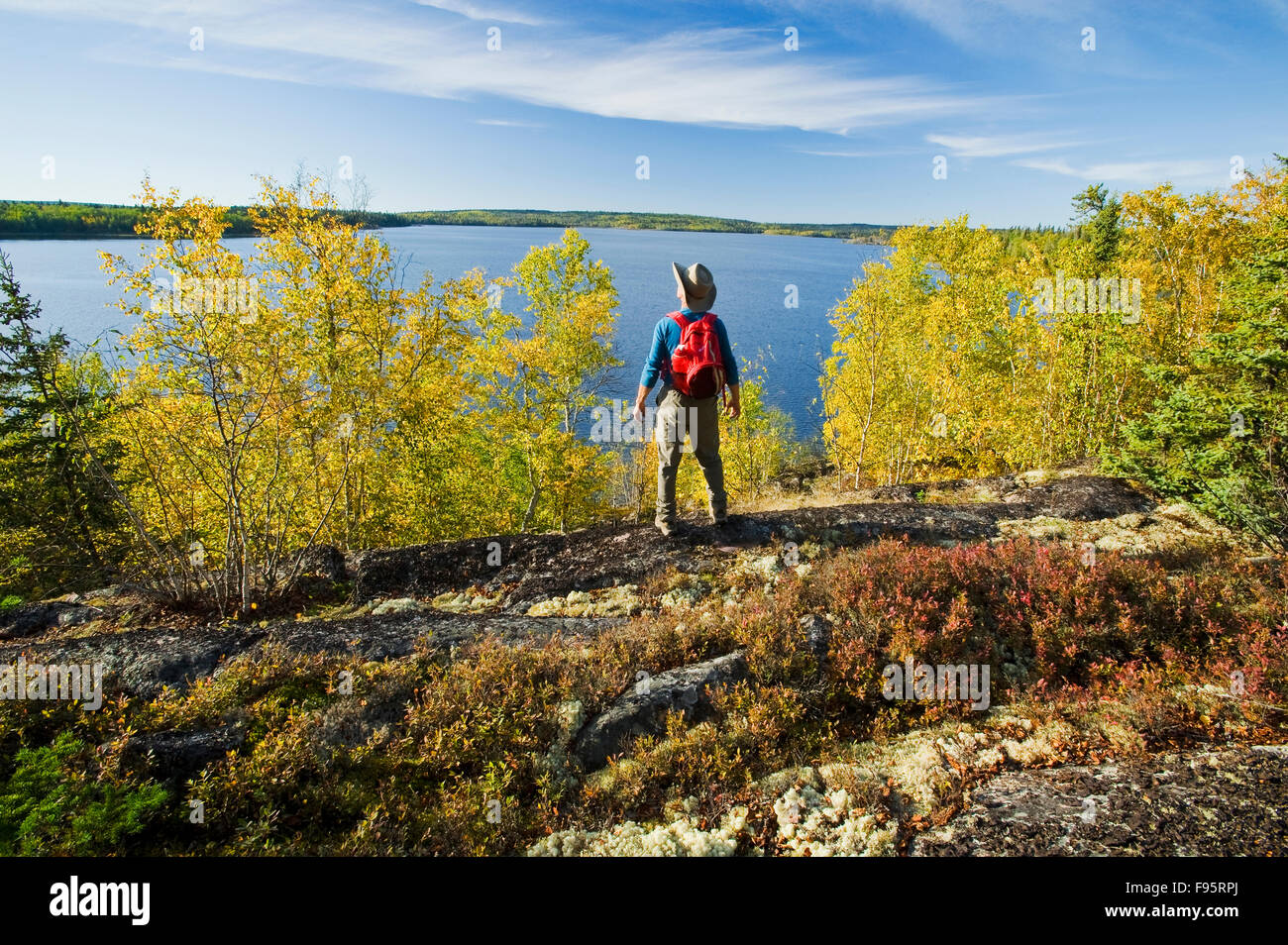hiker looking out over Devil Lake, Northern Saskatchewan, Canada Stock Photo