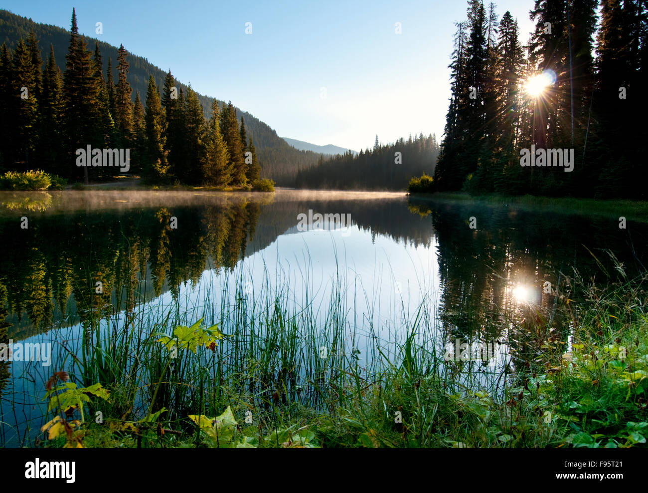 The late summer sun rises over Lightning Lake in Manning Park, BC and provides a spectacular reflection. - Stock Image