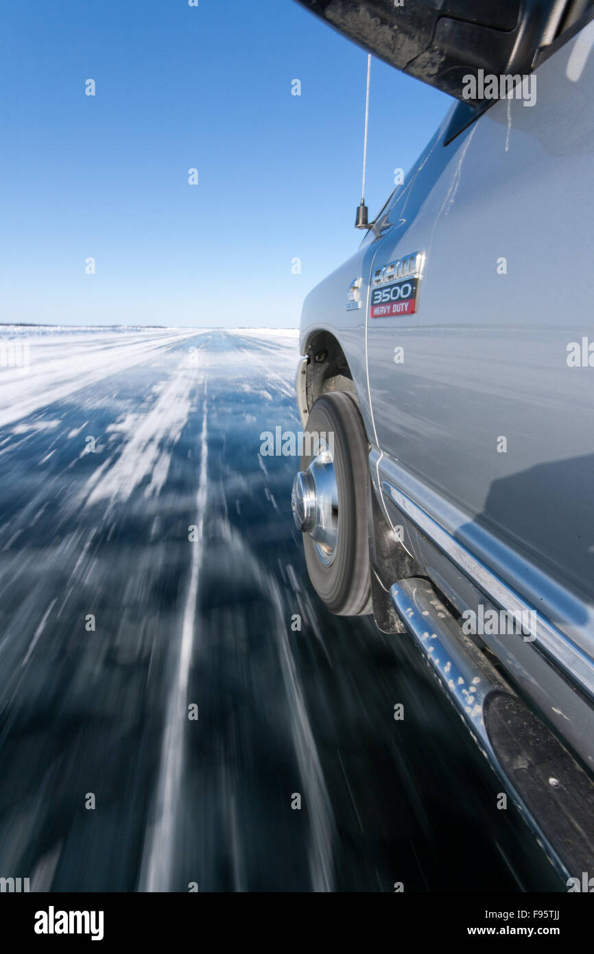 A truck drives on an ice road in the Northwest Territories, Canada. - Stock Image