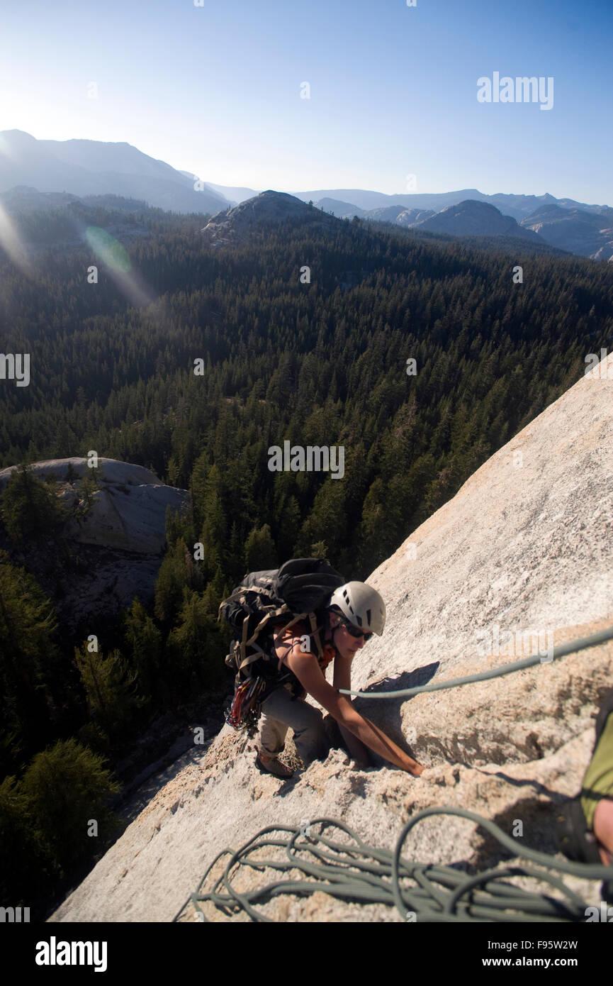 A woman climbing a granite dome in Tuolumne Meadows CA. Stock Photo