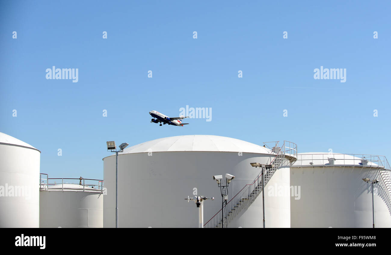 A British Airways passenger jet is seen taking off behind the fuel storage tanks at Heathrow Airport in London Stock Photo