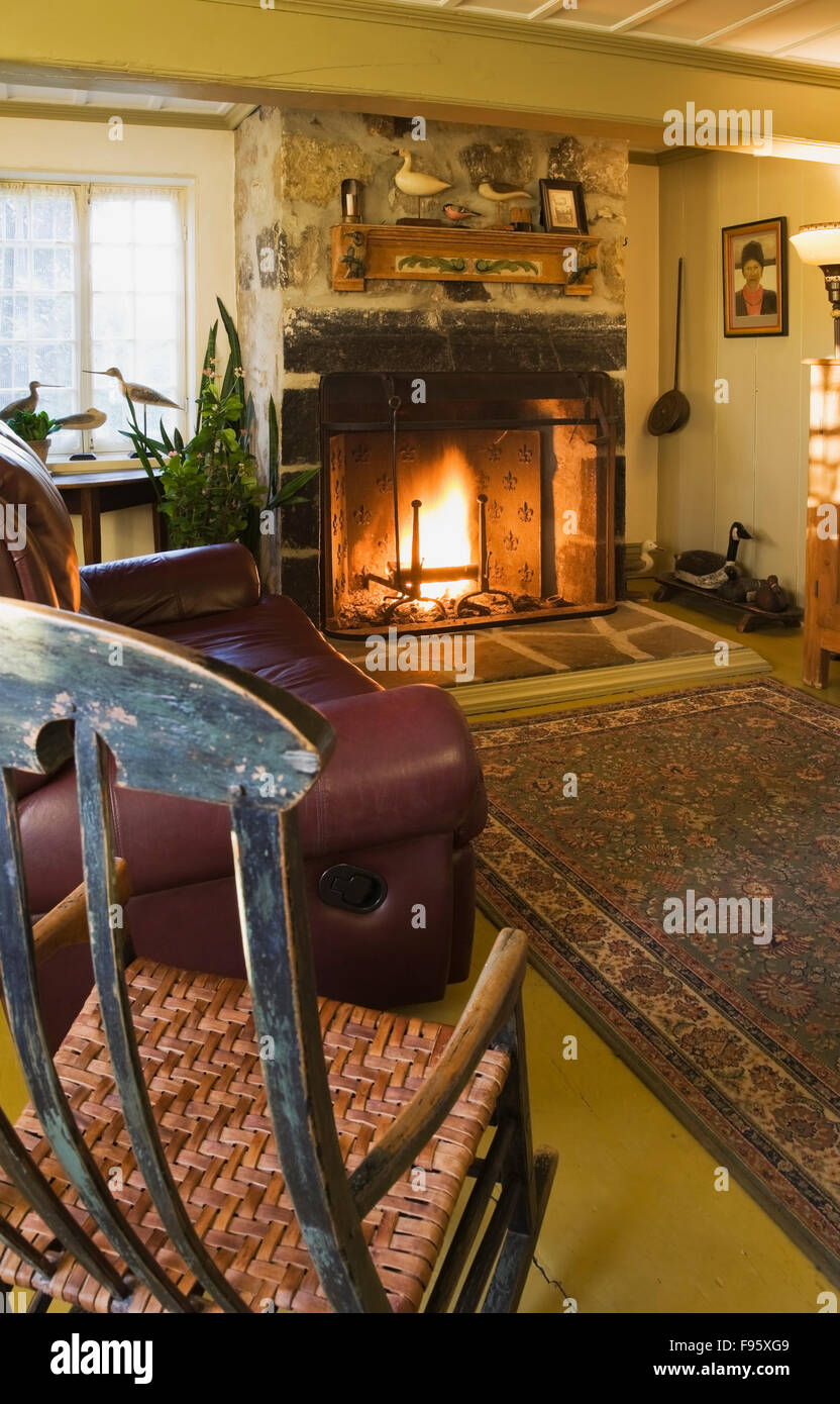 Antique Rocking Chair And Leather Sofa With Lit Fireplace In The Living  Room Inside An Old (1722) French Regime Residential