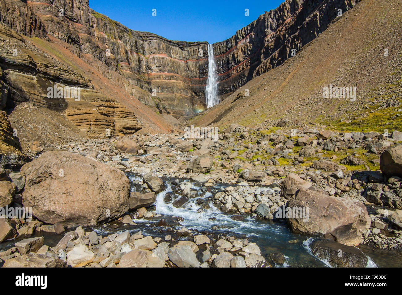 Hengifoss waterfall surrounded by basaltic strata with thin, red layers of clay and the Hengifossá river in - Stock Image