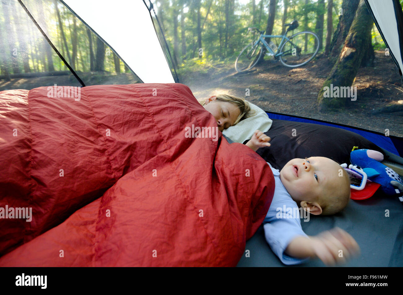 A young mother and her one year old boy in a tent on a camping trip. Mom is still trying to sleep. Rosebery Provincial - Stock Image