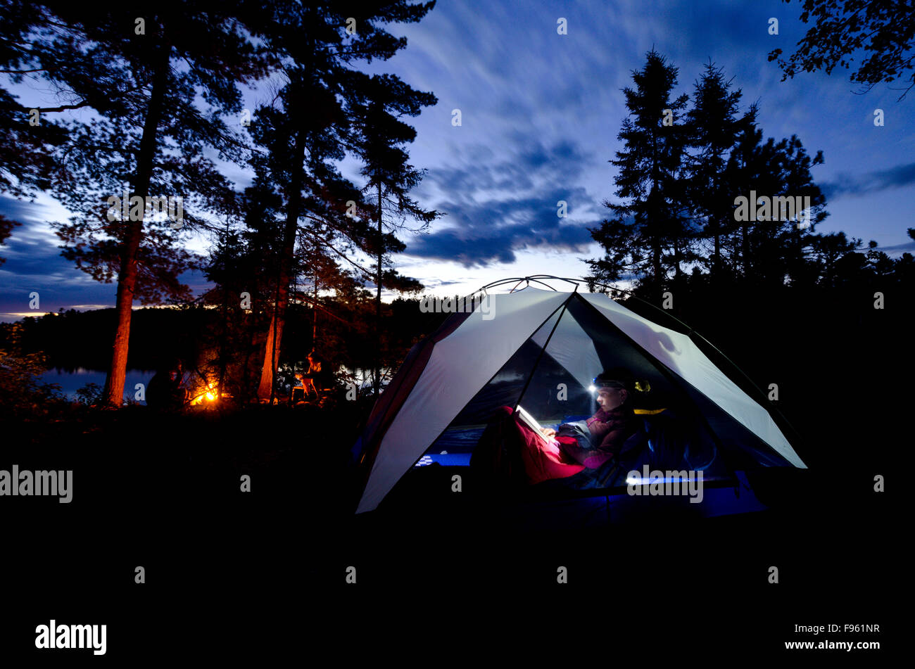 Reading a book at night during a camping trip in Killarney Provincial Park, Ontario Stock Photo