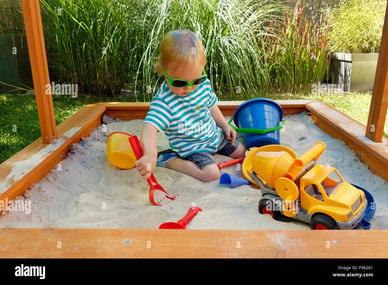 Toddler, girl playing in sandbox, Germany - Stock Image
