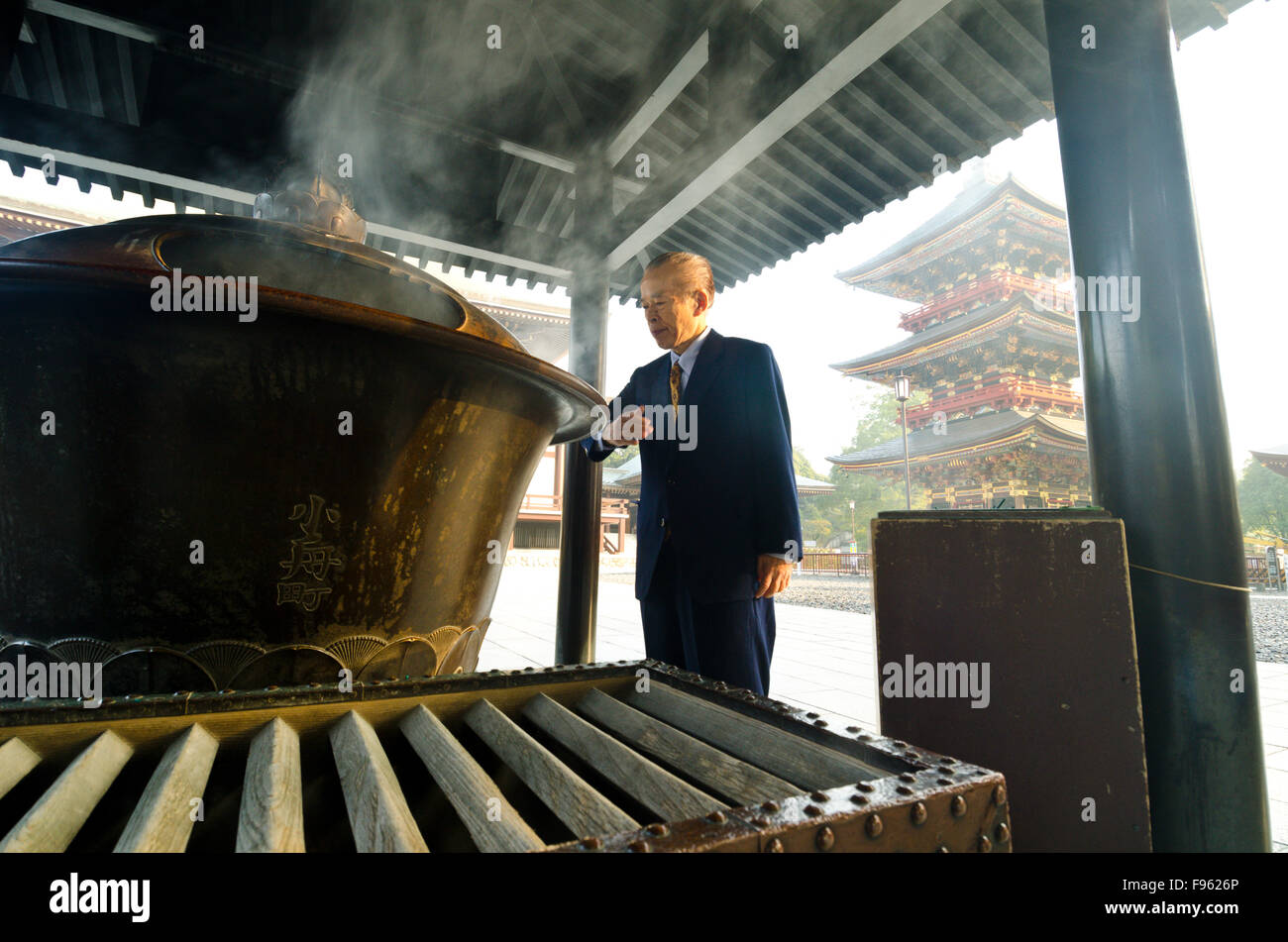 A businessman pauses to inhale soothing fumes at the Shinshoji Temple in Narita, Japan - Stock Image