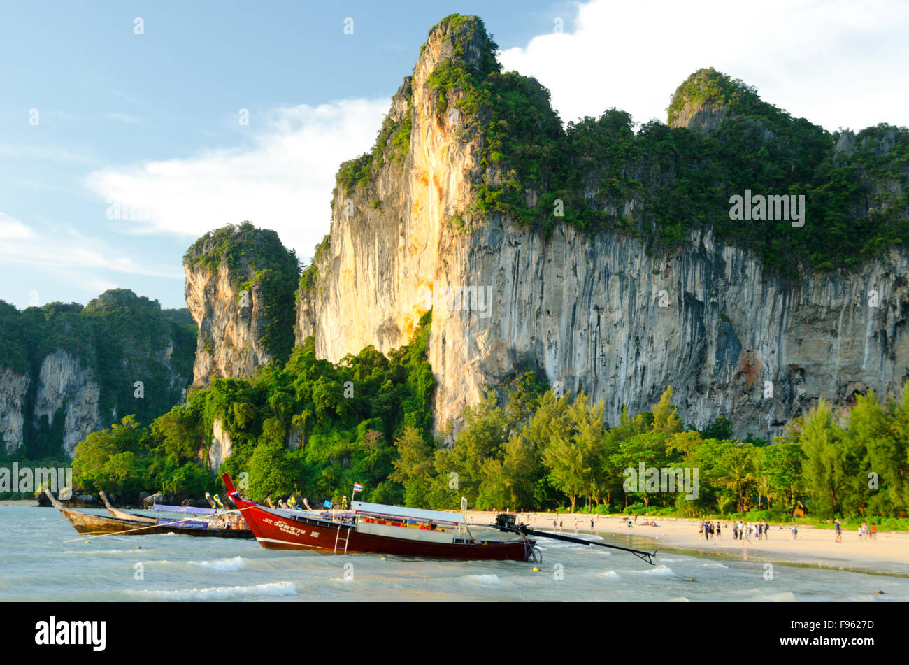 Longtailed boats moored at Railay Beach, Thailand, while tourists wander at sunset - Stock Image