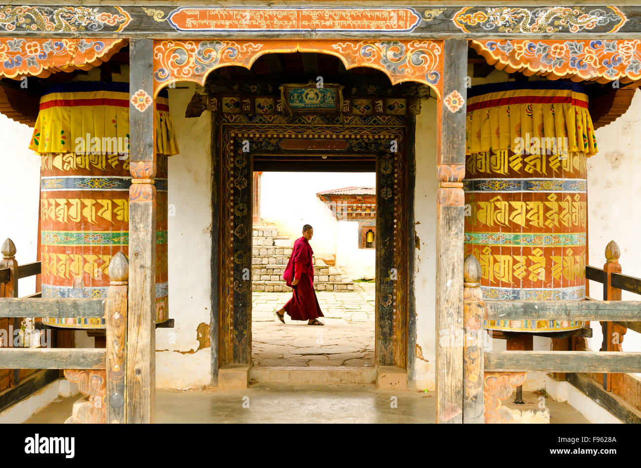 A monk passing by the front doors of Bhutanese monastery - Stock Image