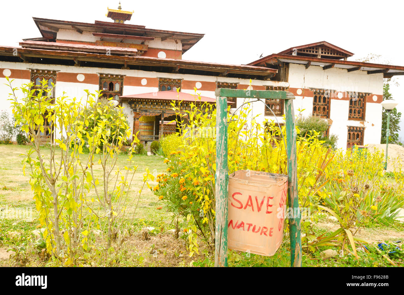 A trash can in front of a Bhutanese monastery  indicates the local mantra - Stock Image