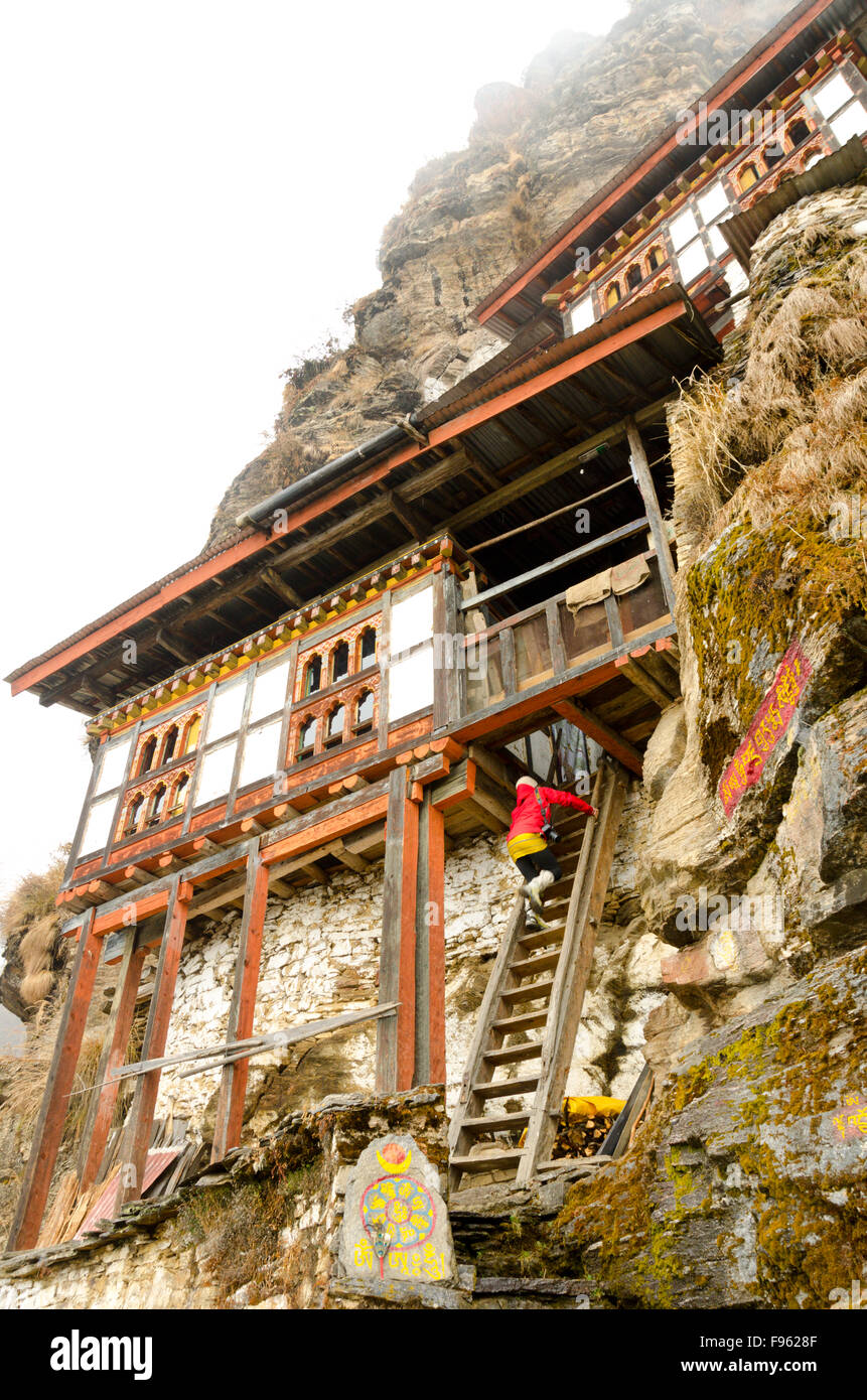 A woman climbs a staircase to a monastery at Bhumdra, Bhutan - Stock Image
