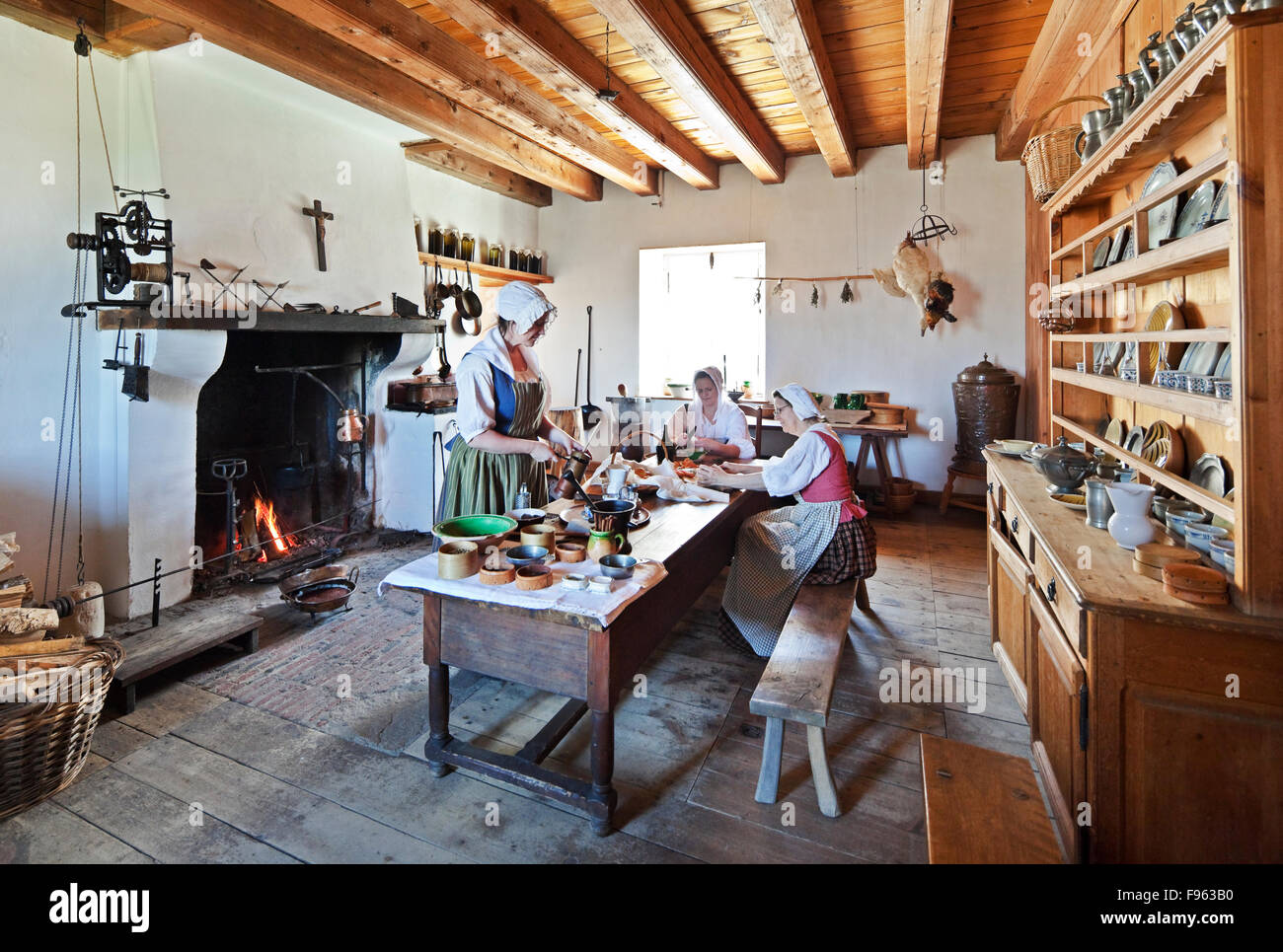 Three women in servant's costumes reenacting a scene of everyday life at 18th Century Fortress of Louisbourg. - Stock Image