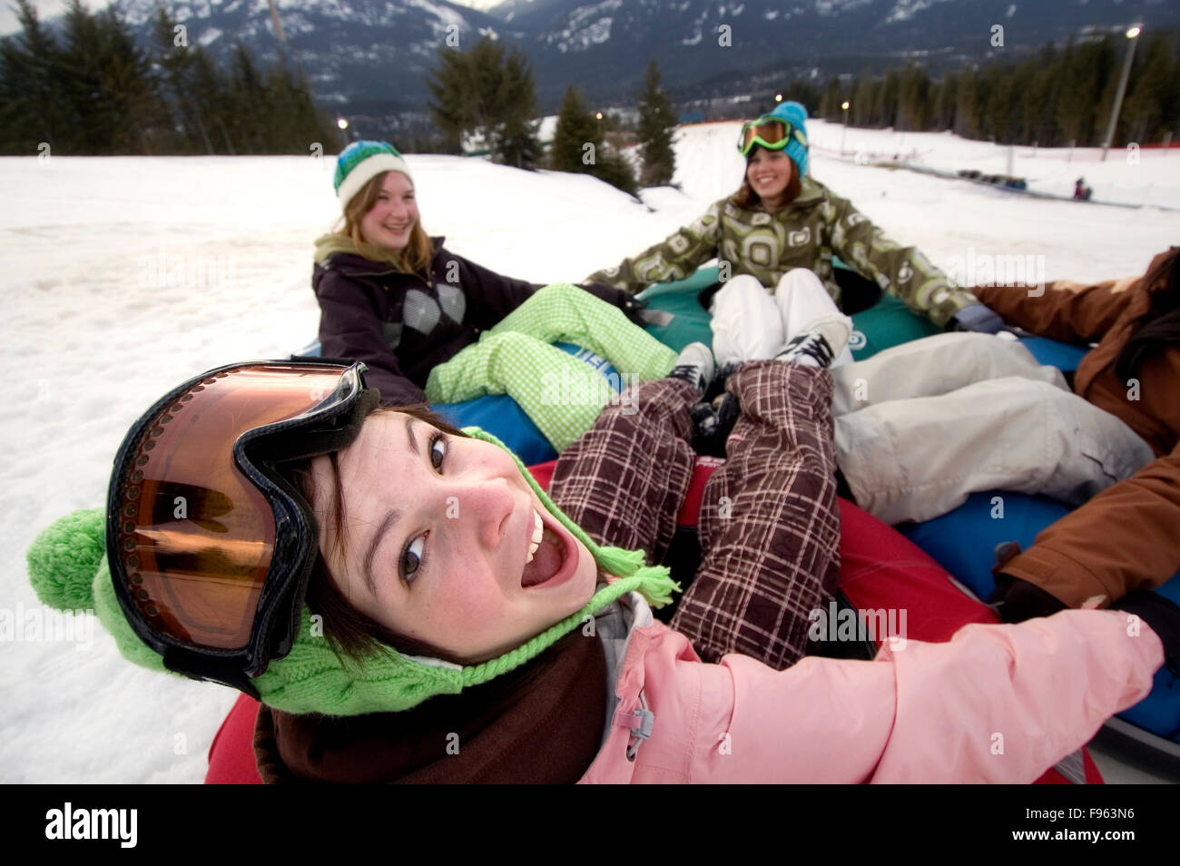 Girls laugh while playing on a giant tube at Whistler Blackcomb Tube Park, Whistler, BC Canada Stock Photo