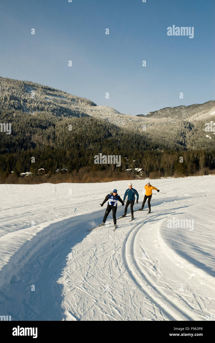 Cross country skiers Maria Lundgren, Morgan Beatty and Munro Duncan skate the trails at Green Lake, part of the - Stock Image