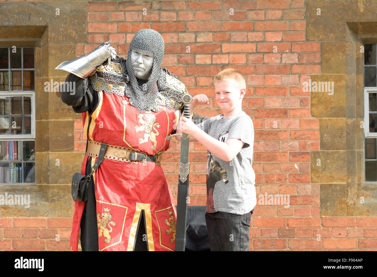 Knight street performer posing with large sword and child in Stratford upon Avon, Warwickshire, England - Stock Image