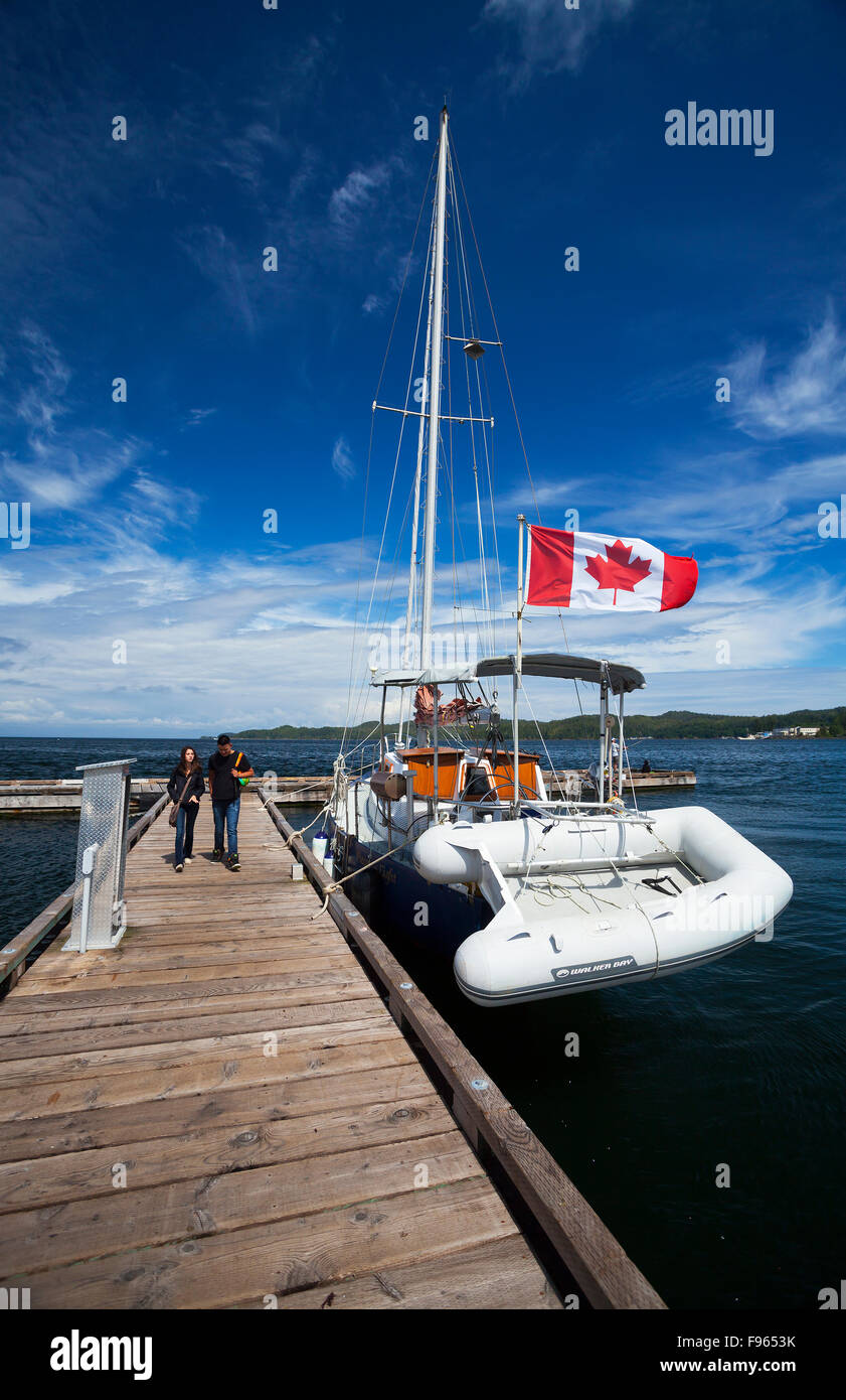 A young couple strolls by a sail boat and an unfurreled Canadian Flag on Port Hardie's wharf walkway. - Stock Image
