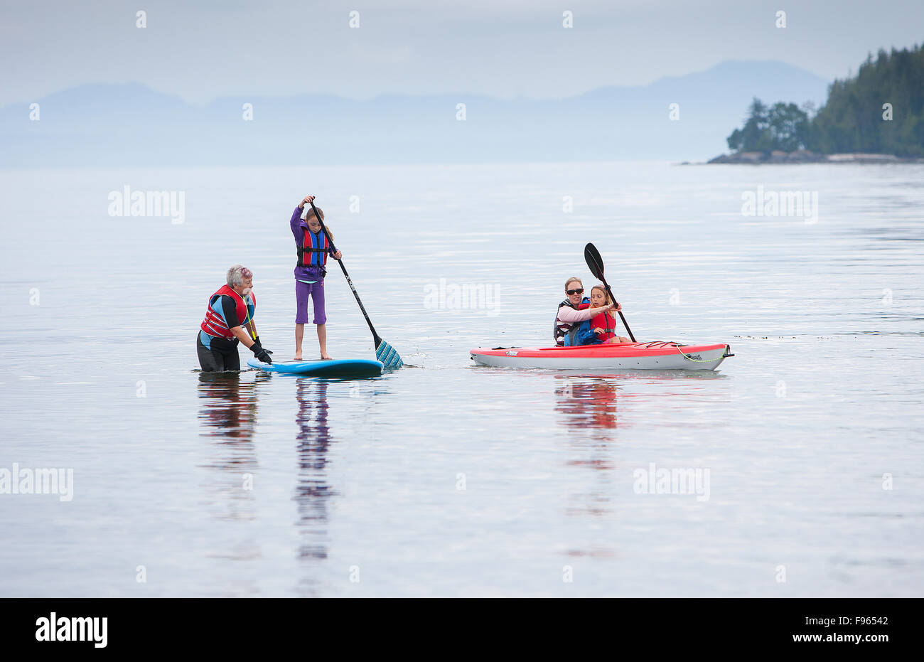 Three generations of women enjoy watersports at Stories Beach near Port Hardy. - Stock Image